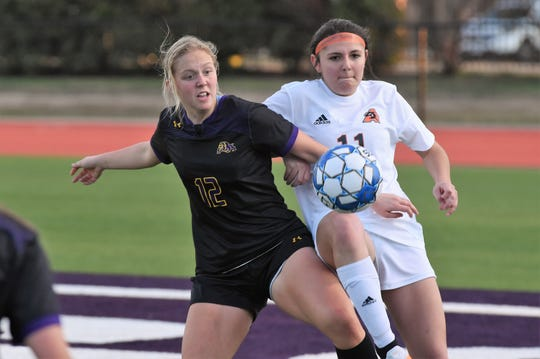 Wylie's Kaitlyn Via (12) battles Aledo's Grace Ornelas (11) for the ball during the District 4-5A opener at Bulldog Stadium on Wednesday. The Lady Bulldogs fell 3-1.