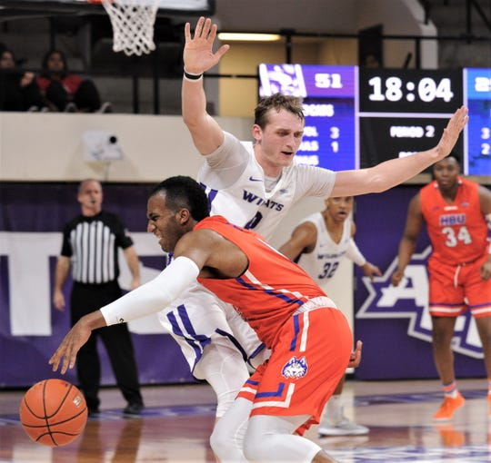 ACU's Clay Gayman defends against Houston Baptist's Ian DuBose in the second half.