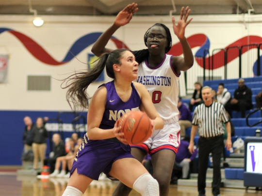 North Kitsap's Mia McNair goes to the basketball while being defended by Washington's Nye Quik during Wednesday's district tournament game.
