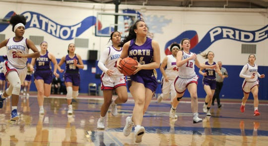 North Kitsap's Noey Barreith eyes the basketball while being pursued by Washington player during Wednesday's district playoff girls basketball game.