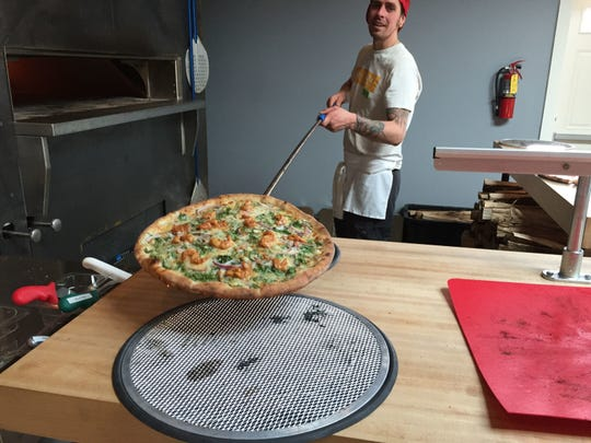 Folino's Pizza employee Bobby Seaman takes a Fire Kracker Shrimp pizza out of the oven at the restaurant in Burlington in 2018.