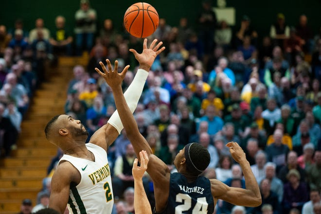 Vermont's Daniel Giddens (2) leaps over New Hampshire's Jayden Martinez (24) for the opening tip off during the men's basketball game between the New Hampshire Wildcats and the Vermont Catamounts at Patrick Gym on Wednesday night February 12, 2020 in Burlington, Vermont.