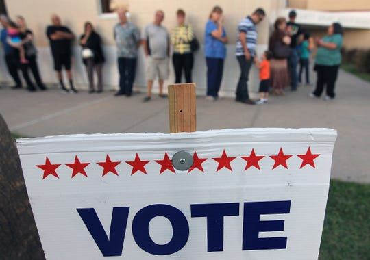 Voters wait in line to cast their ballots