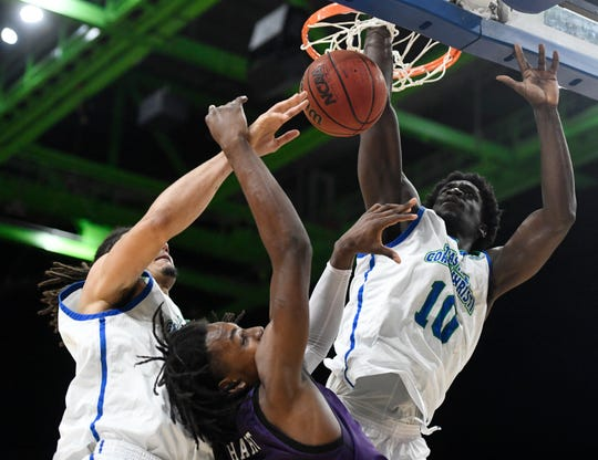 The Islanders' Perry Francois, right, reaches through the hoop to block Stephen F. Austin's basket, Wednesday, Feb. 12, 2020, at the American Bank Center. Stephen F. Austin won, 75-67.