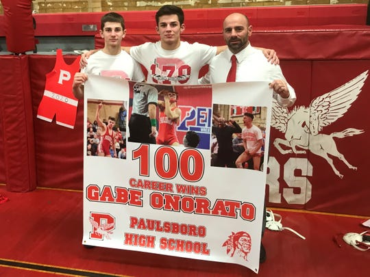 Paulsboro's Gabe Onorato (center) is flanked by his brother Dante and father Bob after celebrating his 100th career win on Wednesday.