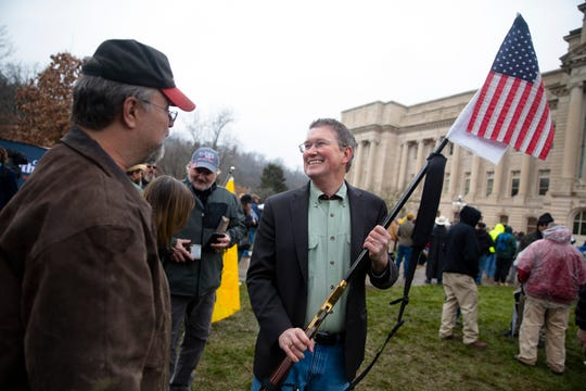 U.S. Rep. Thomas Massie holds Gary Glass's gun after greeting him at a second amendment rally outside the Kentucky State Capitol building in Frankfort, Ky. on Friday. Jan. 31, 2020.