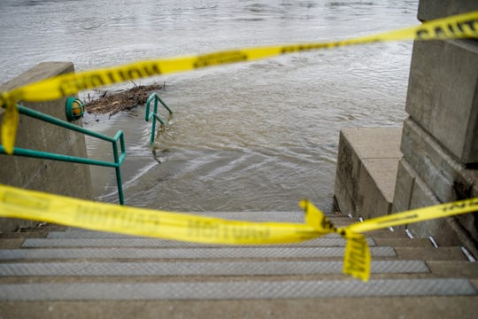 Caution tape floats across the stairs leading down to high waters rushing by bent hand rails at McGregor Park and Riverwalk in Clarksville, Tenn., on Thursday, Feb. 13, 2020.