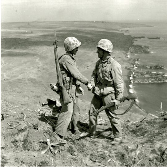 "Cpl. Harold ""Pie"" Keller, right, shakes hands with Sgt. Howard Snyder, left, as they stand on the rim of Mount Suribachi on Iwo Jima between the first and second flag raisings on Feb. 23, 1945. (Official U.S. Army photo, courtesy Pfc. George Burns, George Burns Collection, U.S. Army Heritage and Education Center)"