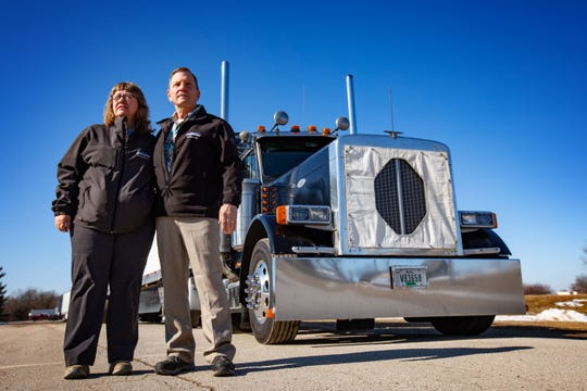 Al and Kym Hemerson stand for a photo next to the semi truck they drive Tuesday, Feb. 11, 2020.