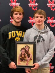 Colby Schriever, left, and Cullan Schriever pose with a photo of themselves at a much younger age during their signing day ceremony at Mason City High School in November.