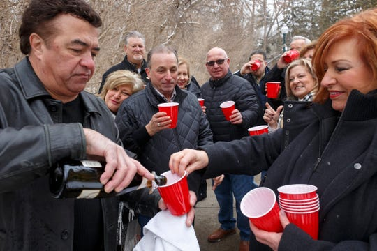 """After posing for a group portrait, Steve Kuclo, left, opens a bottle of champagne and his wife, Geri Kuclo, far right, passes out cups to share with their friends on Sun., February 9, 2020 in Rochester Hills. """"Another adventure for the friends for life,"""" said Dennis J. Torrey who helped gathered his 12 closest and long-time friends."""