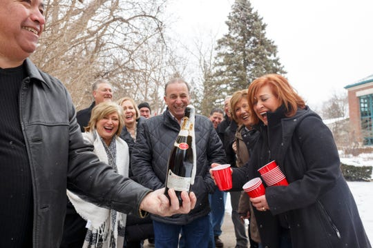 """After posing for a portrait, a group of 13 friends open and share a bottle of champagne on Sun., February 9, 2020 in Rochester Hills. """"Another adventure for the friends for life,"""" said Dennis J. Torrey who helped gathered his 12 closest and long-time friends."""