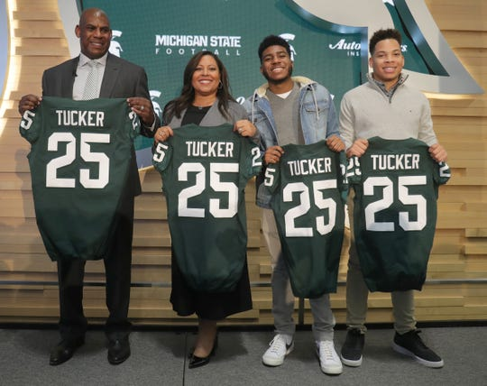 Mel Tucker, his wife Jo-Ellyn, and sons Joseph and Christian, pose with jerseys after Mel was introduced as the new Michigan State football coach Wednesday, Feb. 12, 2020 at the Breslin Center in East Lansing.