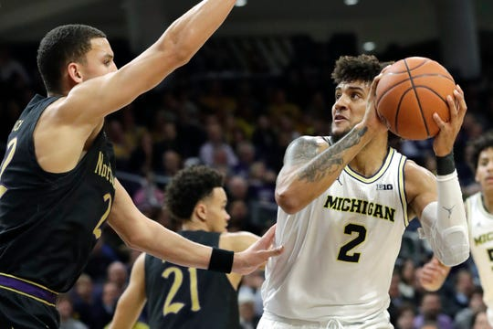 Michigan forward Isaiah Livers, right, looks to the basket against Northwestern forward Pete Nance during the first half of an NCAA college basketball game in Evanston, Ill., Wednesday, Feb. 12, 2020.