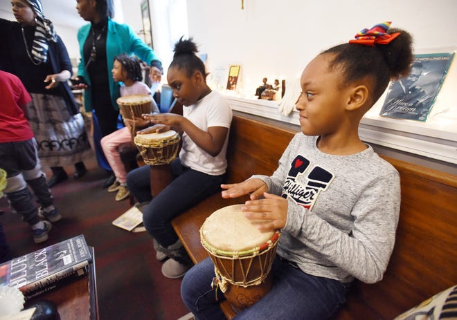 Aubree Windmon, 8, right and Taylor Washington, 9, back, play the drums with students from River of Life Christian School during an African dance Wednesday, Feb. 12, 2020, at the African American History & Literature Gallery in Benton Harbor, Mich. Students visited the gallery to learn about African American history as part of Black History Month.(Don Campbell/The Herald-Palladium via AP)
