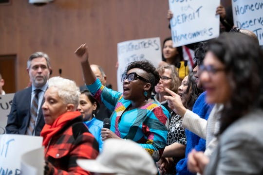 Bernadette Atuahene, a professor at the Chicago-Kent College of Law, chants with protestors during a press conference at the Coleman A. Young Municipal Center, in Detroit, February 13, 2020, to announce a class action lawsuit against the city for the over assessment of home values for thousands of home owners.