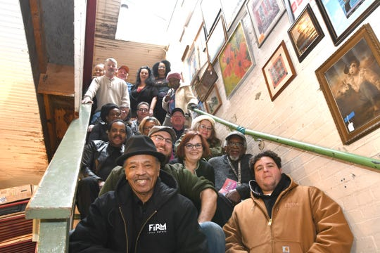 Longtime vendors at Eastern Market Antiques gather on the staircase on  the final day of business on Jan. 25. The store is rebranding to Vintage Eastern Market and has moved around the corner to Division.