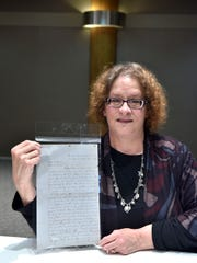 Mary Lyle Olson, of Birmingham, poses with a legal brief signed by Abraham Lincoln before he became president.