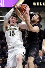 Jon Teske, left, and Zavier SImpson recorded their 104th career victory Wednesday night in the Wolverines' victory at Northwestern.