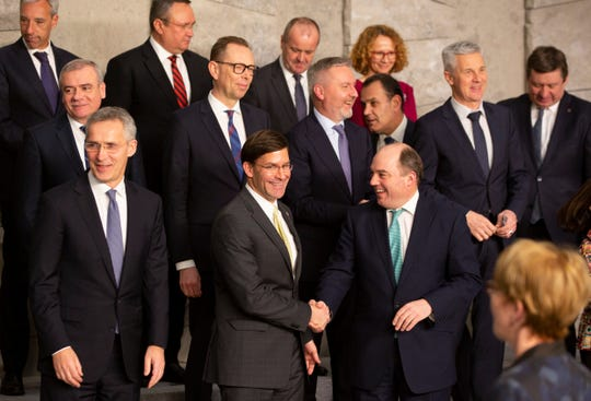 U.S. Secretary for Defense Mark Esper, front center, shakes hands with British Defense Minister Ben Wallace during a group photo of NATO defense ministers at NATO headquarters in Brussels, Wednesday, Feb. 12, 2020.