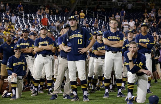 Michigan baseball players watch as Vanderbilt celebrates its national championship in June.