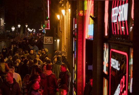 Tourists bathing in a red glow emanating from the windows and peep shows' neon lights are packed shoulder to shoulder as they shuffle through the alleys in Amsterdam's red light district.