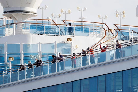 Passengers stand on the deck of the Diamond Princess cruise ship anchored at Yokohama Port in Yokohama, near Tokyo, Wednesday.