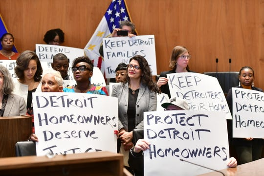 U.S. Congresswoman Rashida Tlaib, center, attends a rally at the Coleman Young Municipal Center in Detroit on Thursday to announce a class action lawsuit against the city for the overassessment of home values for thousands of homeowners.