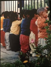 Family photo showing children at an orphanage in Bolivia watching cars go by outside in 2003.