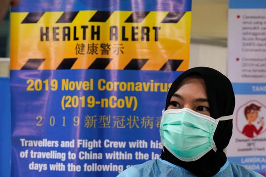 A health official wearing a protection suit and a face mask waits for passengers at a cruise ship terminal in Port Klang, Malaysia, Thursday, Feb. 13, 2020.