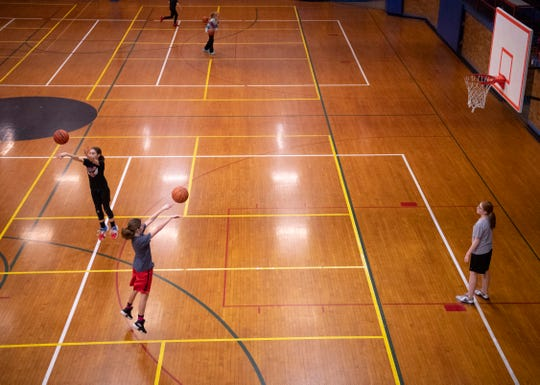 Ambition Basketball players, from left, Caidence Crane, 11, and Tessa Hogan, 13, both of Evansville, run through three-point drills as Rylee Canaan, 11, right, rebounds at the old Downtown YMCA Wednesday night.