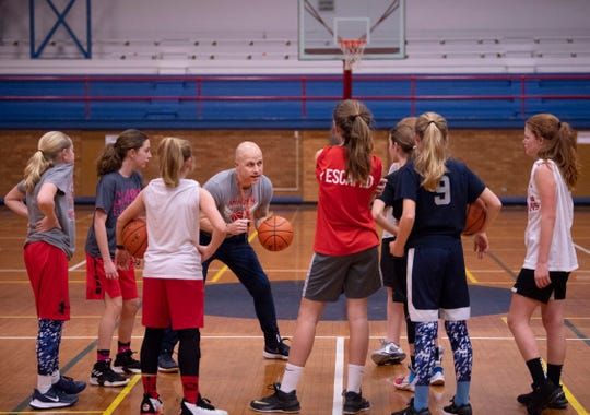 Coach Mitch Lewis gathers his 12U girls Ambition Basketball team to learn a new offense at the old Downtown YMCA Wednesday night.