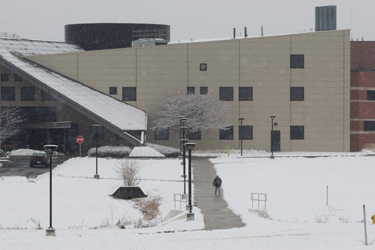 A student walks from the Landings at Terra Village to the Terra State Community College campus Thursday, as snow blanketed the area. Terra State remained open for classes, in spite of the snow.