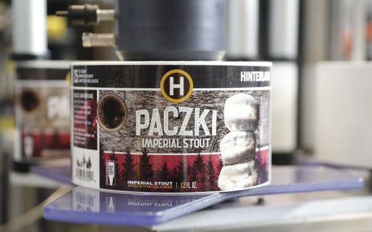 Labels for Hinterland Brewery's new Pączki Imperial Stout are wrapped around the cans Wednesday in Ashwaubenon.