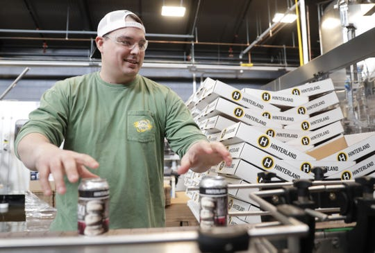 Aaron Briski, brewer for Hinterland Brewery, packages cans of Pączki Imperial Stout on Wednesday at Hinterland Brewery in Ashwaubenon.
