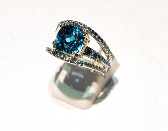 A ring with blue zircon, blue diamond and 18k white gold made by Llyn Strong.
