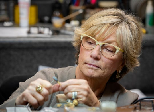 Llyn Strong works on jewelry at her studio and store in downtown Greenville.