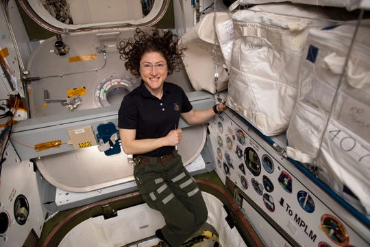 In this June photo made available by NASA, astronaut Christina Koch poses for a portrait inside of the vestibule between a SpaceX Dragon cargo craft and the Harmony module of the International Space Station. S