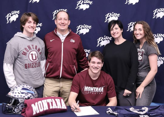 Great Falls High running back Gabe Longin (seated) signs his college letter-or-intent to play at the University of Montana. Surronding him are, from left, brother Rafe, father Tony, mother Collette, and sister Amelia.