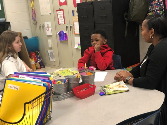 Haywood Elementary students Abby Scott and Braden Woodland discuss reading text with the teacher's assistant Jasmine Perkins.
