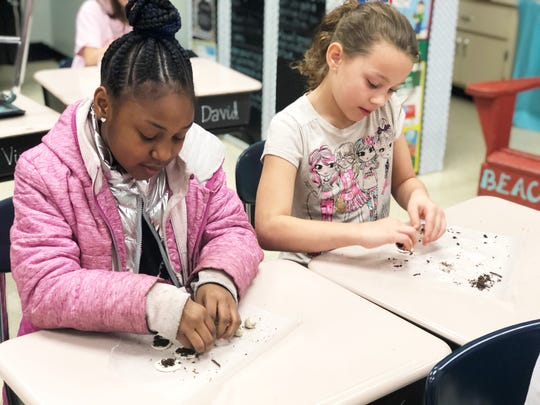 """Third graders Damary Harper, left, and Ghillian Silva sprinkle soil and wildflower seeds onto a disc of air dry clay, before rolling it into a """"seed bomb"""" as a Valentine's Day gift at New Hopewell Elementary School on Feb. 12, 2020. """"I love planting at my house and I put them outside for my environment,"""" Ghillian said."""