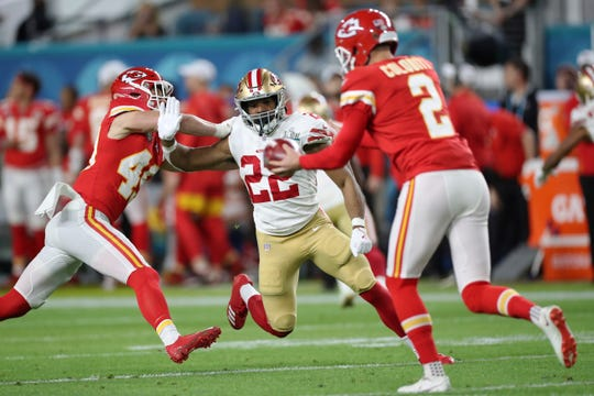San Francisco 49ers running back Matt Breida (22) rushes Kansas City Chiefs punter Dustin Colquitt (2) in Super Bowl 54, Sunday, Feb. 2, 2020 in Miami Gardens, Fla. The Chiefs defeated the 49ers 31-20. (AP Photo/Doug Benc)