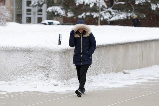 Jaimie Diedam, a freshman human services major, shields herself from the wind as she walks across Purdue University's campus, Thursday, Feb. 13, 2020 in West Lafayette.