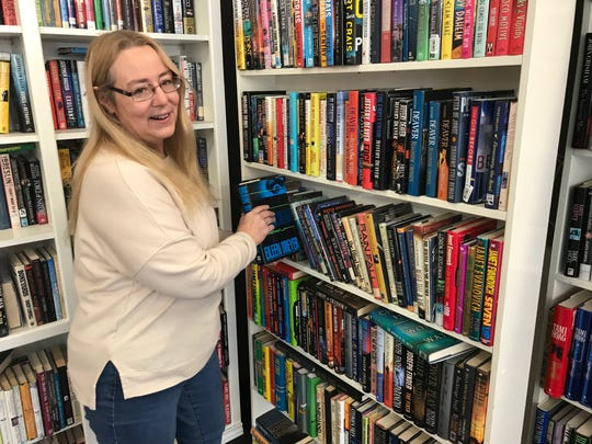 Paperback Exchange own Leanne McClellan is surrounded by just some of the hundreds of books in stock at her used book store at the corner of Main and Columbus streets.