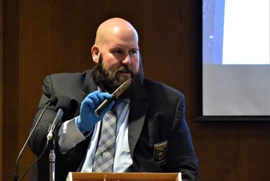 Ohio Bureau of Criminal Investigation Agent Todd Fortner holds a fixed blade aloft during the jury trial for Chad Kerens Feb. 12. The knife was recovered from Kerens' apartment, found with blood on the blade and handle. Kerens is accused of murdering one man and attempting to destroy and tamper with evidence.