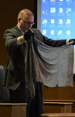 Lancaster Police Detective Kurt Humbert holds a shirt worn by defendant Chad Kerens up to the jury during Kerens' murder trial Feb. 13. Kerens is accused of killing one man and destroying or tampering with evidence to hide that crime.
