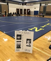 Former Hartland wrestling coach Bill Cain, who died Friday, was honored with an empty chair and a poster beside the mat for the district tournament on Wednesday, Feb. 12, 2020.