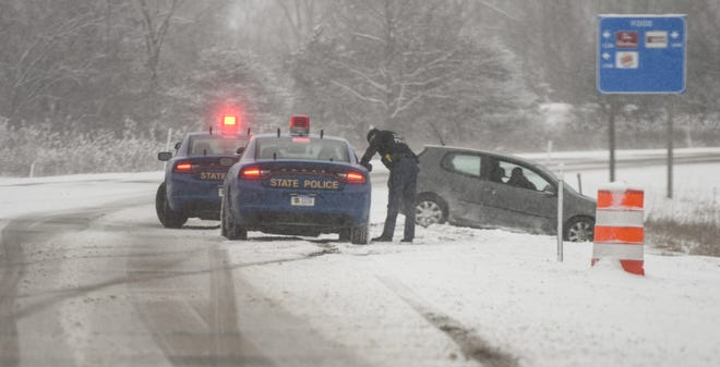 State police attend to a vehicle stuck in a ditch on I-496 near Creyts Road on Thursday afternoon, Feb. 13, 2020.