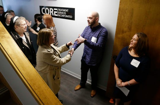 Chris Gilbert, co-executive Director, left, and Carmen Persaud, co-executive Director, right, greet people visiting CORE Treatment Services, Inc. new facility near Holy Family Memorial, Wednesday, February 12, 2020, in Manitowoc, Wis.