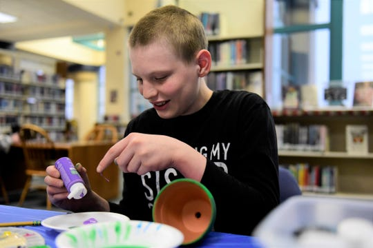 Jordan Houser, 16, of Mansfield, wipes some purple paint from a bottle Thursday before finishing his project.
